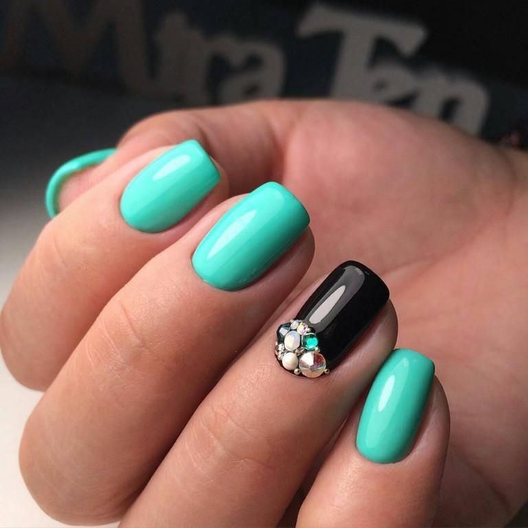 Обворожительный и яркий бирюзовый цвет мгновенно привлекает к себе внимание окружающих. Акцент маникюра – это красивые камни и стразы на безымянном пальце, наклеенные поверх черной глянцевой основы.