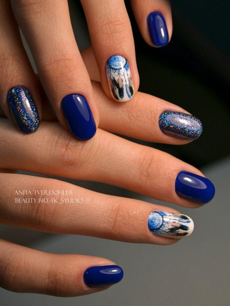 Яркий, блестящий маникюр с оригинальным дизайном. Его оформление выполнено в темно-синих тонах. На указательном пальце темно-синий лак с блестящей основой.