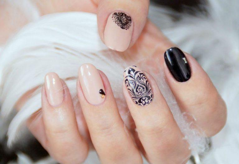 Нежный и женственный маникюр, который совершенно преобразит ваши пальчики, создан на базе молочно-розового лака. Попробуйте придать ногтям элегантную овальную форму. Указательный ноготь можно покрыть черным лаком, а на большом и среднем нанести узоры из черного кружева.