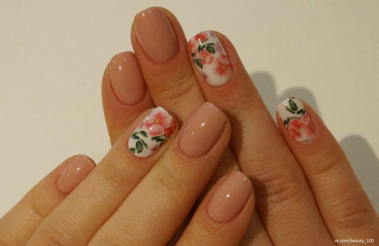 Почему бы не воспользоваться розово-бежевым лаком и самыми простыми цветочными наклейками? Посмотрите, как эффектно выглядят ногти, которые аккуратно подстрижены в полуквадратной форме.