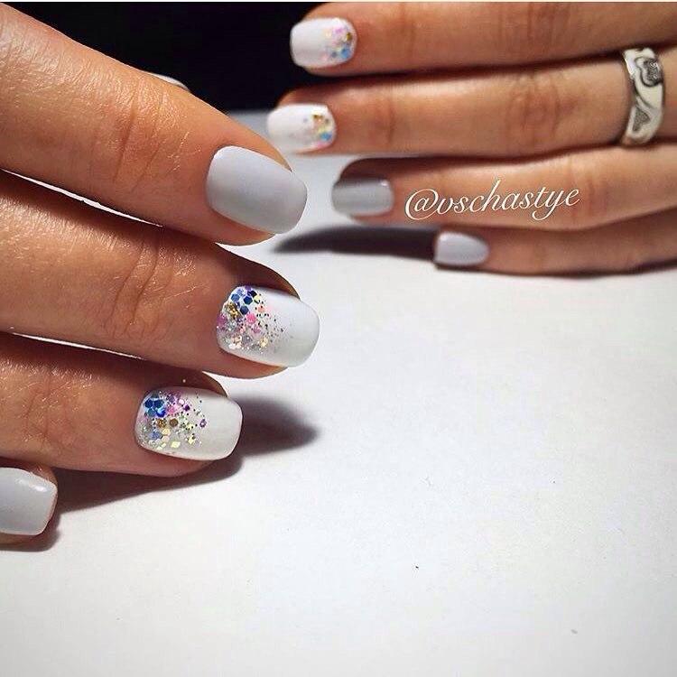 Оригинальный вариант маникюра на короткие ногти. Дизайн выполнен в белом цвете, разбавляет светлый тон разноцветная блестящая пыль, заметно подчеркивая и прибавляя контрастности ноготкам.