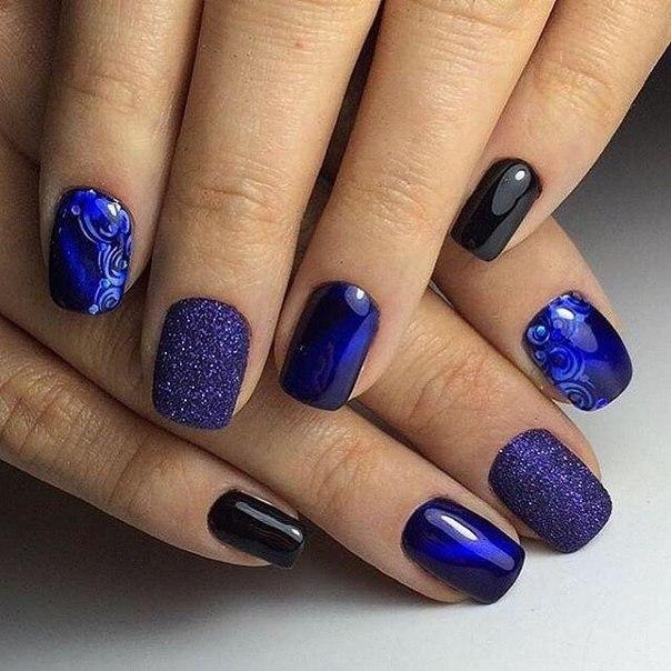 Такой изысканный вечерний маникюр создаст чарующий образ таинственной женщины. Для его создания воспользуйтесь синим и черным лаками, а также акриловым напылением и наклейками. Ногти покрываются разноцветными лаками в произвольном порядке – главное, чтобы результат был симметричным для обеих рук. Черный и синий оттенки всегда создают нужный эффект, а напыление с искорками и несколько мелких голубых стразов дополнят картину.