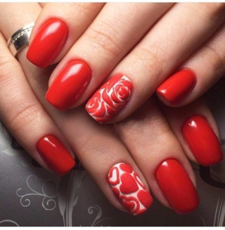 Акценты на двух ногтях выполнены в контрастном сочетании матовых лаков белого и красного цвета. Для создания эффектного узора можно воспользоваться наклейками или техникой нейл-арта.