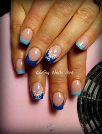 Нарядный французский маникюр с широкой улыбкой выполнен светло-голубым и синим лаком. Ровный срез ногтей подчеркнут яркими цветами полосок, едва заметными блестками в синеве.