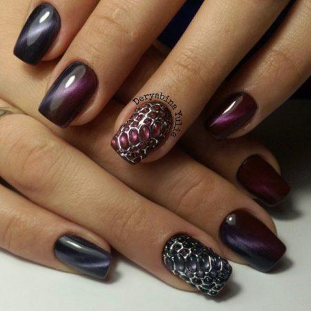 Змеиный дизайн покрытия на безымянных пальцах выполнен с помощью акрила, модного серебристого лака. Оттенок металлик придает узору холодноватый отлив, выделяет рельефный рисунок. Богатая гамма сиреневых тонов дарит ноготкам пурпурный блеск, манит фиолетовыми переливами.
