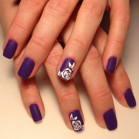 Изысканный маникюр спокойного оттенка фиолетового, украшенный лаконичным цветочным рисунком. Изюминкой композиции становится актуальное в последнем сезоне матовое топовое покрытие.