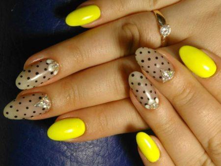 Желтый яркий маникюр на миндалевидной форме ногтя с оригинальным дизайном черного горошка