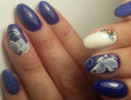 Синий маникюр с дизайном украшен бисером камнями и стразами