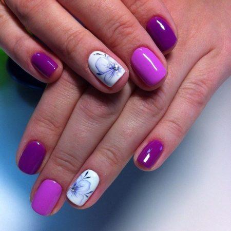 Глубокий фиолетовый резко контрастирует с белоснежным цветом и привлекает к себе внимание. Главная деталь белого ноготка – нежный распустившийся цветок со стразом в центре.