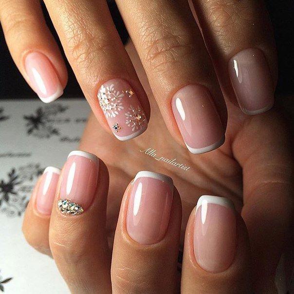На коротких ногтях бело-розовый френч выглядит очень изысканно и аккуратно. Акцент делается на безымянном пальце. Белым цветом прорисовывается красивая кружевная снежинка, которая дополняется блестящими стразами разной величины.