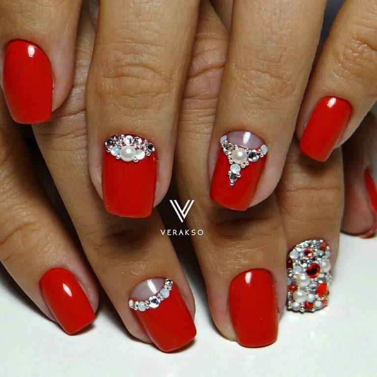 Красный маникюр будет великолепно выглядеть на ногтях любой формы. В данном случае они оформлены в форме квадрата. Чтобы сделать дизайн максимально нарядным, мастер нейл-арта использовал элементы техники лунного маникюра и отделку стразами.