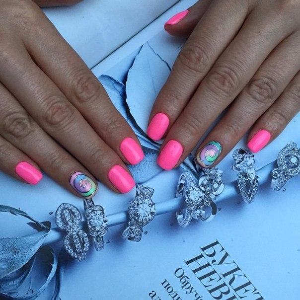 Ногти покрываются кислотным розовым лаком. На ногте безымянного пальца можно использовать технику сложного градиента, совмещенную с рисунком, или просто воспользоваться наклейкой. Маникюр отлично смотрится в любой сезон.