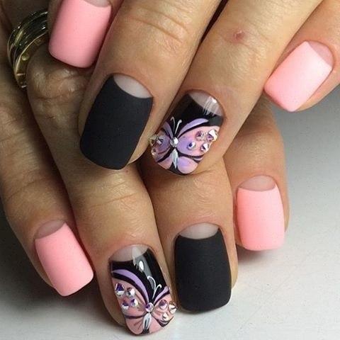 Ногти не обязательно должны быть длинные, нужно лишь придать им форму квадрата. Лунки оставьте нетронутыми, для всего остального пространства ногтей используйте поочередно бледно-розовый и черный матовые лаки. Красивые наклейки с рисунком и стразами дополнят дизайн.