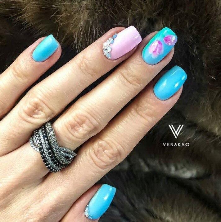 Ногти окрашиваются лаком голубым, безымянный – исключение, для него используется розовый лак. На ногте среднего пальца можно нарисовать цветы или воспользоваться наклейкой. Ногти большой и безымянный украшаются стразами у самого основания.