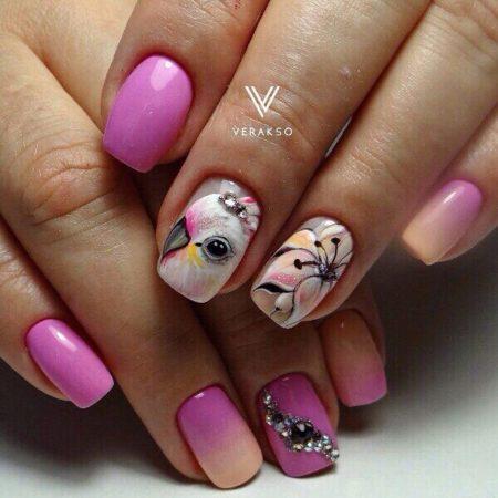 На безымянном и среднем пальцах нанесено изображение попугая и красивого цветка. Эффектно завершает яркий дизайн блестящие стразы уложенные волной.