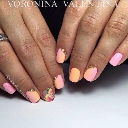 Градиентный маникюр в розово-желтой гамме смотрится очень легко и нежно. Плавный переход таких цветов выглядит, словно розовый закат и радует глаз своей обладательнице. На одном из ногтей рисуется кистью красивый фиолетовый цветок.