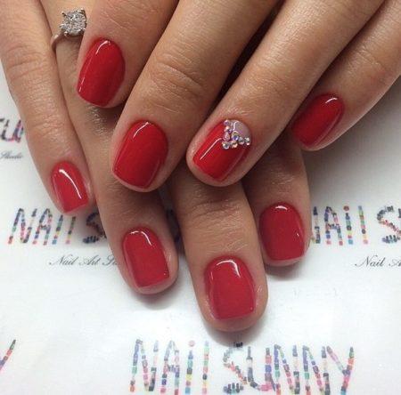 Идеальный глянцевый красный украшен лаконичным узором на безымянном пальце. Для дизайна использованы крупные прозрачные стразы, расположенные в виде треугольника у основания ногтя.