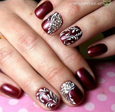 Бордовый вечерний маникюр на короткие ногти с рисунком и стразами