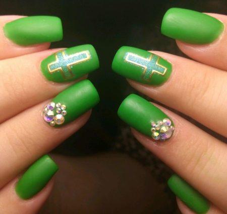 Матовый зеленый маникюр с крестами и стразами на квадратной форме ногтя